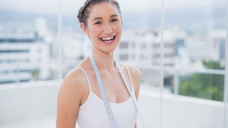 Smiling sporty brunette holding measuring tape
