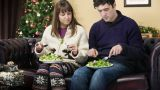 Couple eating salad on sofa