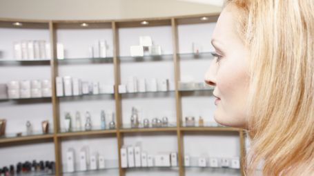 Woman Looking at Shelf of Cosmetics
