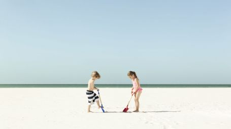 Brother (5-6) and sister (5-6) playing on beach