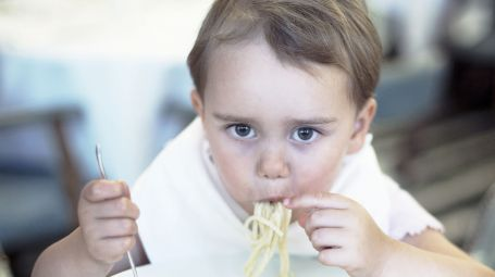 Boy (2-3) eating spaghetti
