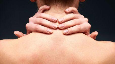 donna di spalle che si tocca il collo