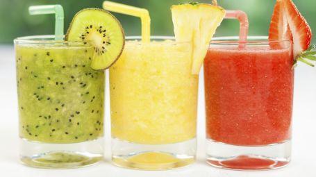 tre bicchieri con tre smoothie, uno verde, uno giallo e uno rosso