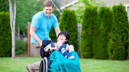 bambino con padre su sedia a rotelle
