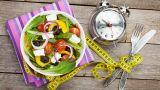 piatto con insalata mista, orologio e misurino da sarto