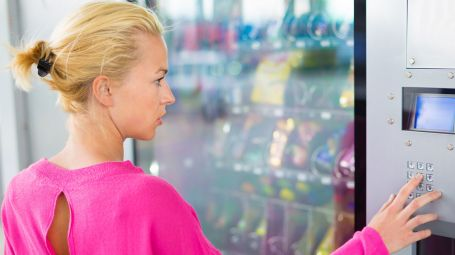 ragazza bionda davanti a distributore di merendine
