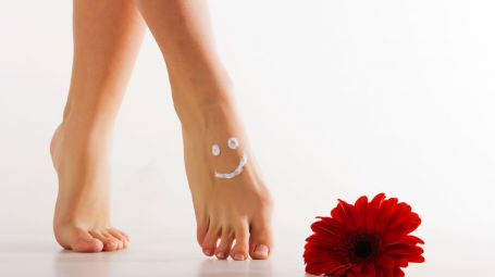 piedi femminili curati, incrociati e in punta. Vicino c'è un fiore rosso