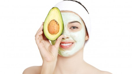 Pretty woman holding an avocado over her clay facial mask