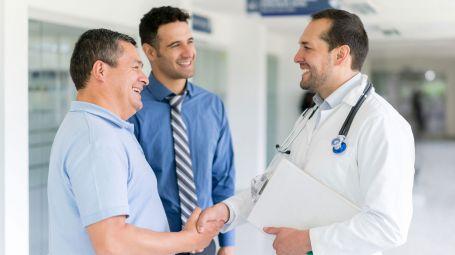 medico stringe la mano a un paziente accompagnato