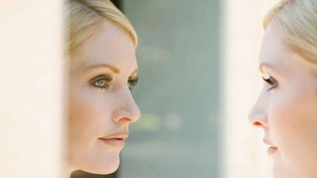 donna di profilo che si guarda allo specchio