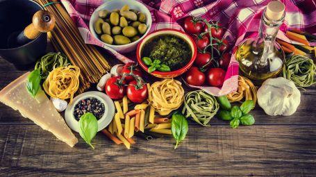 tavolo di legno preso dall'alto con cibi tipidi della dieta mediterranea