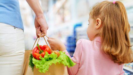 mamme e figlia di spalle fanno la spesa