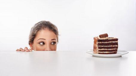donna guarda una fetta di torta