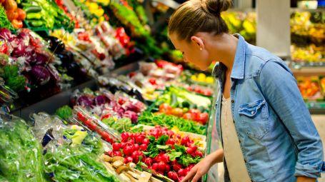 donna davanti al banco di frutta e verdura