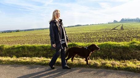 donna sorridente cammina con il cane