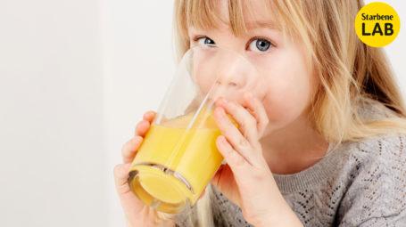 bambina beve succo d'arancia