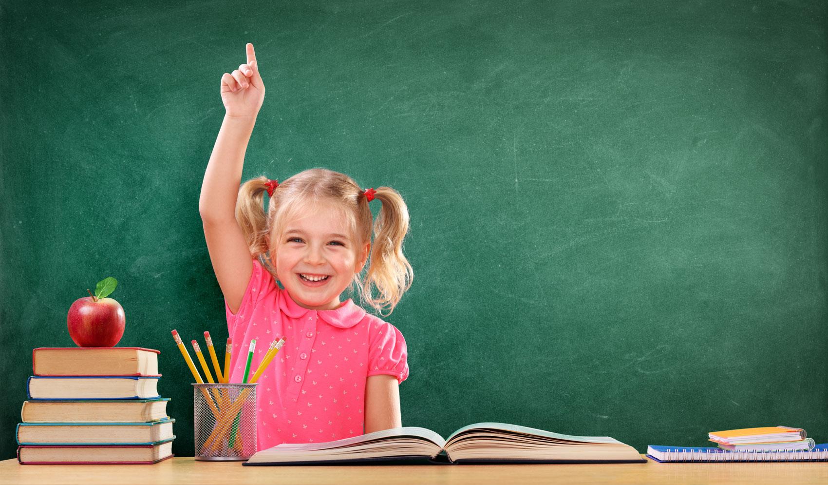 bambina sorridente che alza la mano a scuola