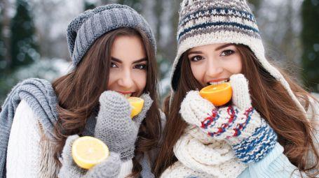 ragazze mangiano arance in montagna
