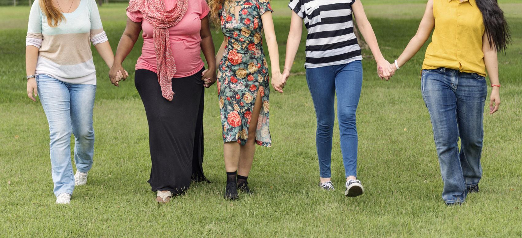 gruppo di donne a mani unite su prato