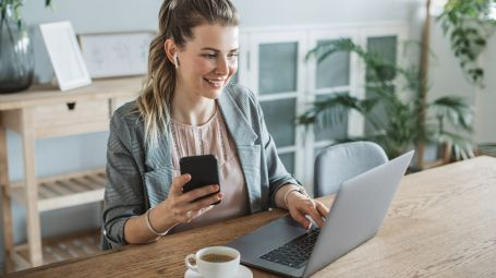 donna in smart working, cellulare, computer, caffè